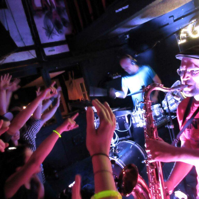 Eine Band auf der Bühne des KNUP und tanzendes Publikum