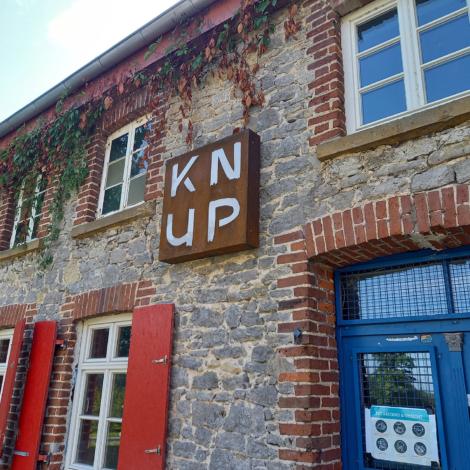 Ansicht: vom KNUP – ein Bruchsteinhaus mit roten Fensterläden